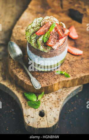Layered healthy breakfast ingredients in glass over rustic board - Stock Photo