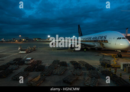 A panorama of planes being are loaded and unloaded on the apron at Heathrow airport in the UK. - Stock Photo