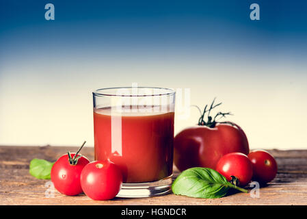Tomato juice and a few small tomatos in the glass on the wooden table. Copy space - Stock Photo