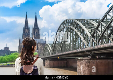 Young woman seen from back looking to rhine river, huge bridge and famous cathedral of Cologne, Germany - Stock Photo