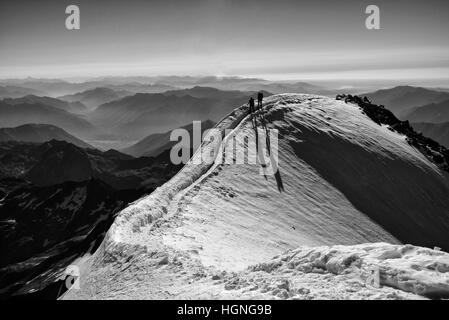 Climbers arriving at the summit of the Weissmies - Stock Photo