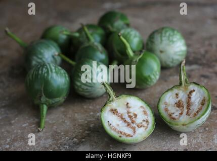 A bunch of Thai eggplants, with one cut in half. - Stock Photo