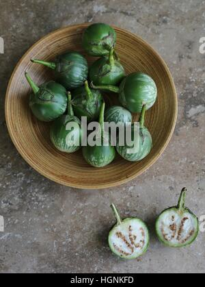 A bowl of Thai eggplants and one cut open in foreground. - Stock Photo