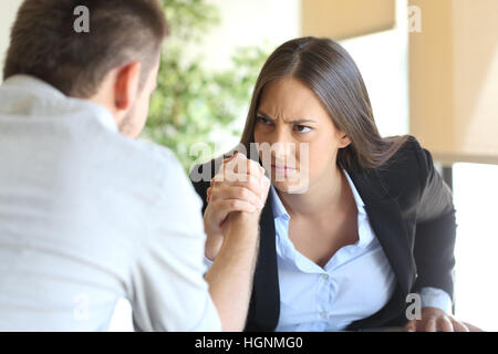 Two angry businessman and businesswoman wearing suit fighting looking each other at office - Stock Photo
