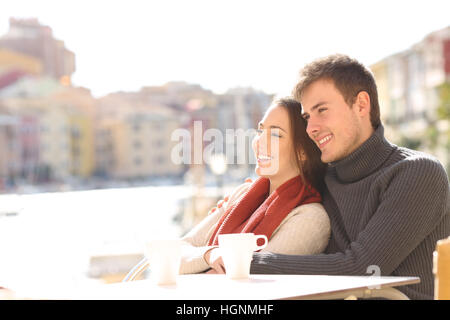 Couple relaxing sitting in an hotel terrace on holidays with a port in the background in a sunny day of winter - Stock Photo