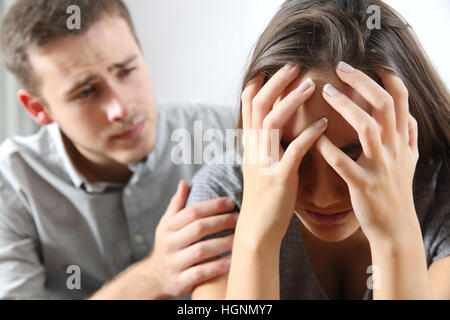 Meeting of a sad woman and a friend or boyfriend trying to comfort her at home - Stock Photo