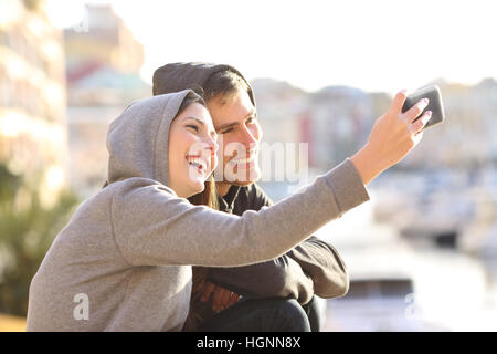 Couple of teens taking a selfie with a smart phone outdoors on holidays with a port in the background - Stock Photo
