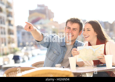 Couple of tourists searching location siting in an hotel terrace during a summer travel with a port in the background - Stock Photo