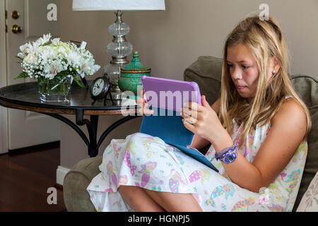 Eleven-year-old Girl Playing a game on iPad. - Stock Photo