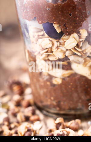 Chocolate chia pudding with oat flakes in the glass jar - Stock Photo