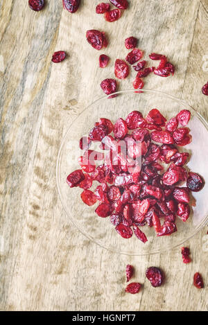 Dried cranberries in the glass bowl on the wooden table - Stock Photo