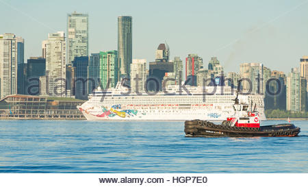 Norwegian Jewel cruise ship guided by a tug boat as it maneuvers into the Canada Place cruise ship terminal in Vancouver, - Stock Photo