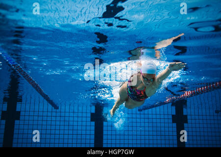 Underwater shot of woman training in swimming pool. Female swimmer in action inside swimming pool. - Stock Photo