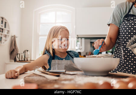 Happy little girl standing in kitchen and her mother cooking food. Mother and happy daughter baking in kitchen. - Stock Photo