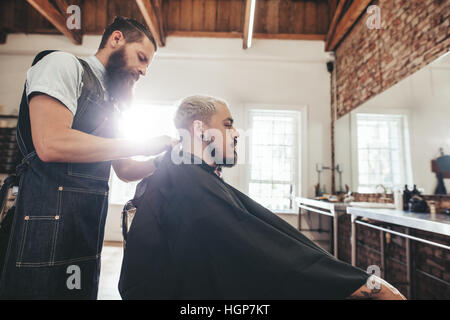 Side view shot of handsome young man getting haircut in salon. Hairstylist serving client in barber shop. - Stock Photo
