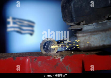One Euro coin in a vice being cut with an angle grinder whilst Greek flag flies in background - Stock Photo