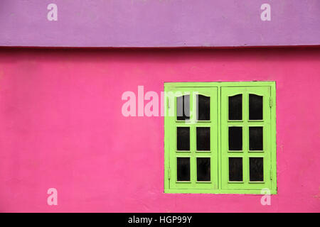 Close up of a brightly colored building with pink walls, lime green windows & purple roof, Caribbean. - Stock Photo