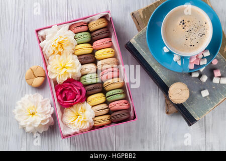 Colorful macaroons and coffee on wooden table. Sweet macarons in gift box and flowers. Top view - Stock Photo