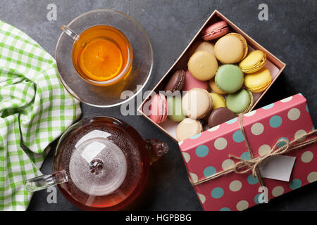 Tea cup, teapot and macaroons gift box on stone table. Top view - Stock Photo