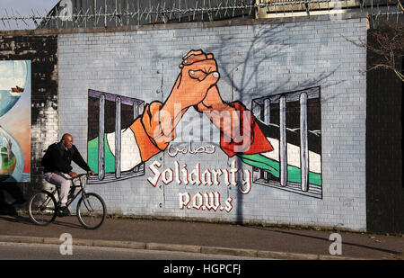 Man cycling in front of the Peace Wall along Northumberland Street in the Falls district of Belfast - Stock Photo
