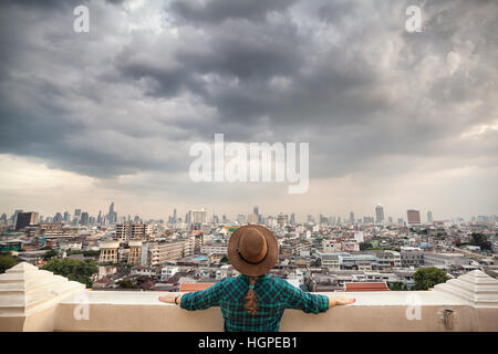 Tourist woman in hat and green checked shirt looking at Bangkok City panorama with skyscrapers of business district - Stock Photo