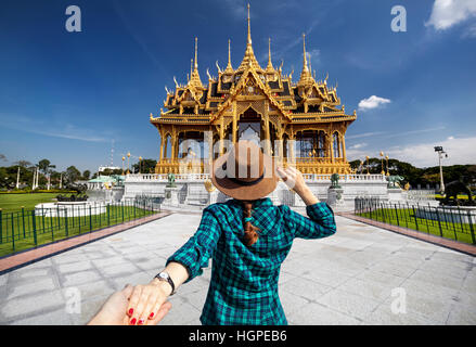 Woman in hat and green checked shirt leading man to the Ananta Samakhom Throne Hall in Thai Royal Dusit Palace, - Stock Photo