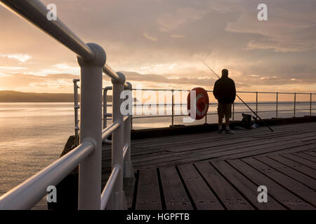 Silhouetted against a dramatic, colourful sky at sunset, one man is sea fishing from the West Pier - Whitby, North - Stock Photo