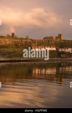 View of the East Cliff (houses, St. Mary's Church, abbey ruins and rainbow) reflected in the sea - Whitby, North - Stock Photo