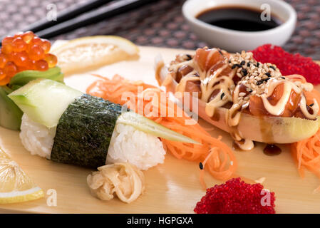 Japanese cuisine sushi set with salmon fish served with tartar sauce on wooden board, close up view - Stock Photo