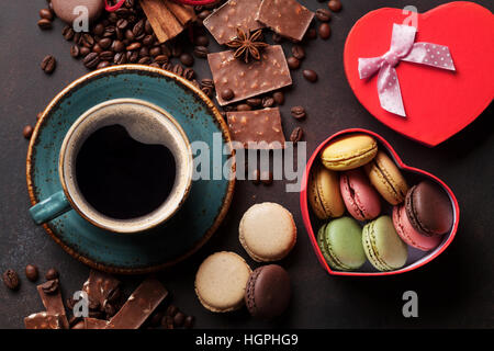 Coffee cup, beans, chocolate, macaroons and gift box on old kitchen table. Top view - Stock Photo