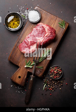 Raw ribeye beef steak cooking with ingredients. Top view - Stock Photo