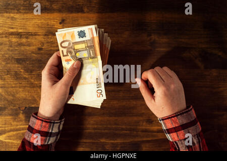 Woman offering money loan in euro currency banknotes, top view of business office desk - Stock Photo
