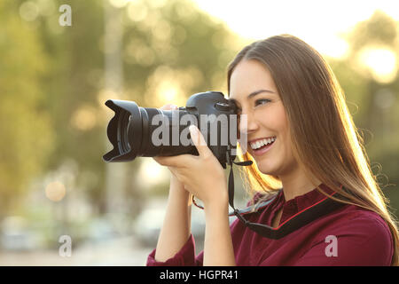 Photographer photographing with a digital camera outdoors at sunset with a warm light - Stock Photo