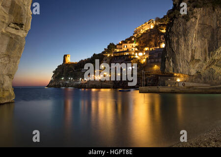Twilight over the tiny beach of Marina di Praiano with Torre a Mare beyond, Praiano, Campania, Italy - Stock Photo
