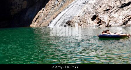 Serpentine,WA,Australia-January 30,2014:Couple floating on an inflatable in the rock pools with waterfall at Serpentine - Stock Photo