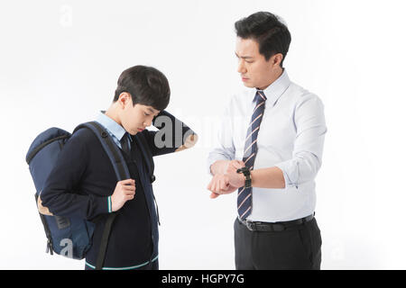 Teacher scolding a school boy for being late - Stock Photo