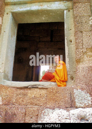Young monk studying in window at Angkor Wat - Stock Photo