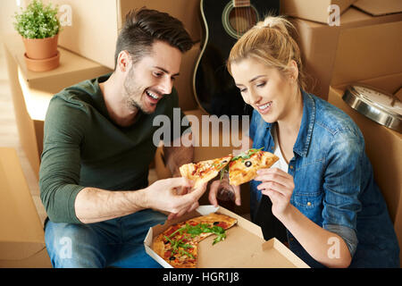 Couple eating pizza next to moving boxes - Stock Photo
