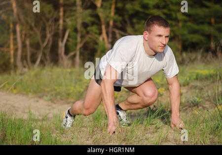 Young athletic man at the start to run outdoors. - Stock Photo