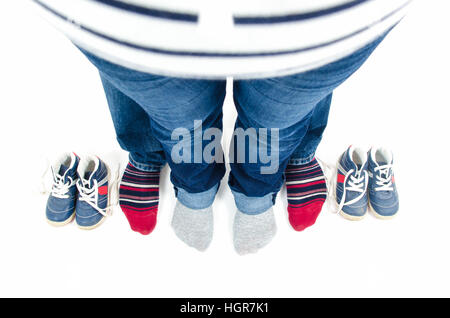 Parents are expecting twins. top view of father and mother feet and baby shoes. Parents are wearing blue jeans and - Stock Photo