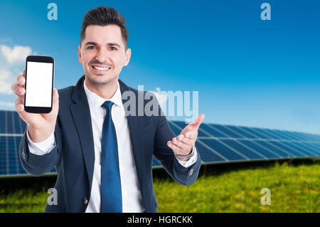 Handsome businessman showing cellphone with blank screen in photovoltaic station as ecological energy concept with - Stock Photo