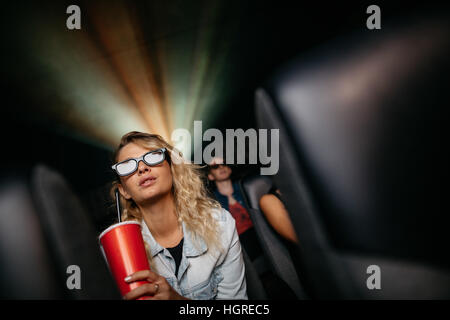 Beautiful young woman with cold drink and 3d glasses watching movie in theater. - Stock Photo