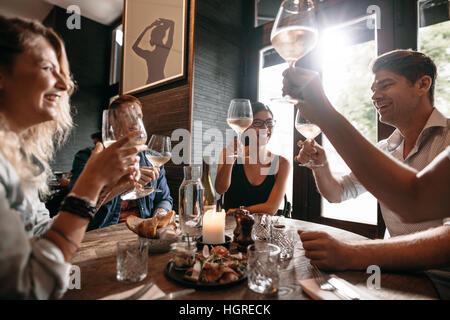 Group of friends making a toast at restaurant. Young people friends sitting at a table, toasting with wine and enjoying - Stock Photo