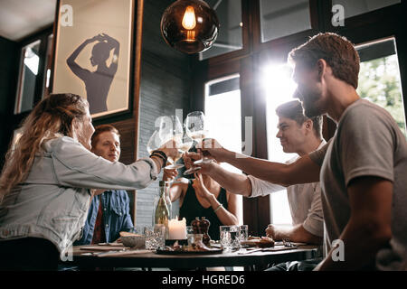 Young man and woman sitting at table and toasting drinks at restaurant. Group of friends toasting wine at cafe.
