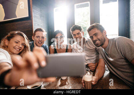 Diverse group of friends taking selfie on smart phone. Young men and women sitting at cafe table and taking a self - Stock Photo