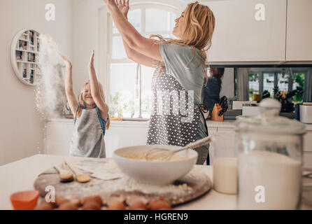 Happy young family having fun in kitchen throwing flour in air. Mother and daughter making dough in kitchen. - Stock Photo