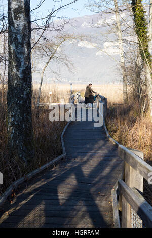 Tourist family & view of Marais de Lavours National Nature Reserve, Ain, France. French pre - Alps mountain in the - Stock Photo