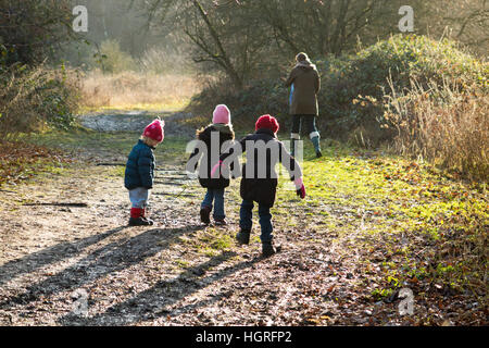 Mother & 3 children three kids daughters walking / walk along muddy path / in mud on walkway pathway foot path footpath - Stock Photo