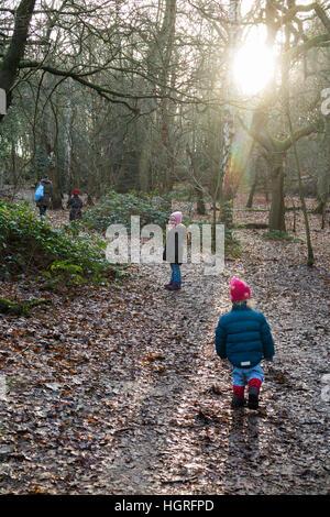 Mother & 3 children three kids daughters walking / walk along muddy path / in mud on walkway pathway foot path footpath - Stock Photo