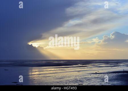 Sun shines behind dark clouds on the beach, Amrum, North Frisia, Schleswig-Holstein, Germany - Stock Photo